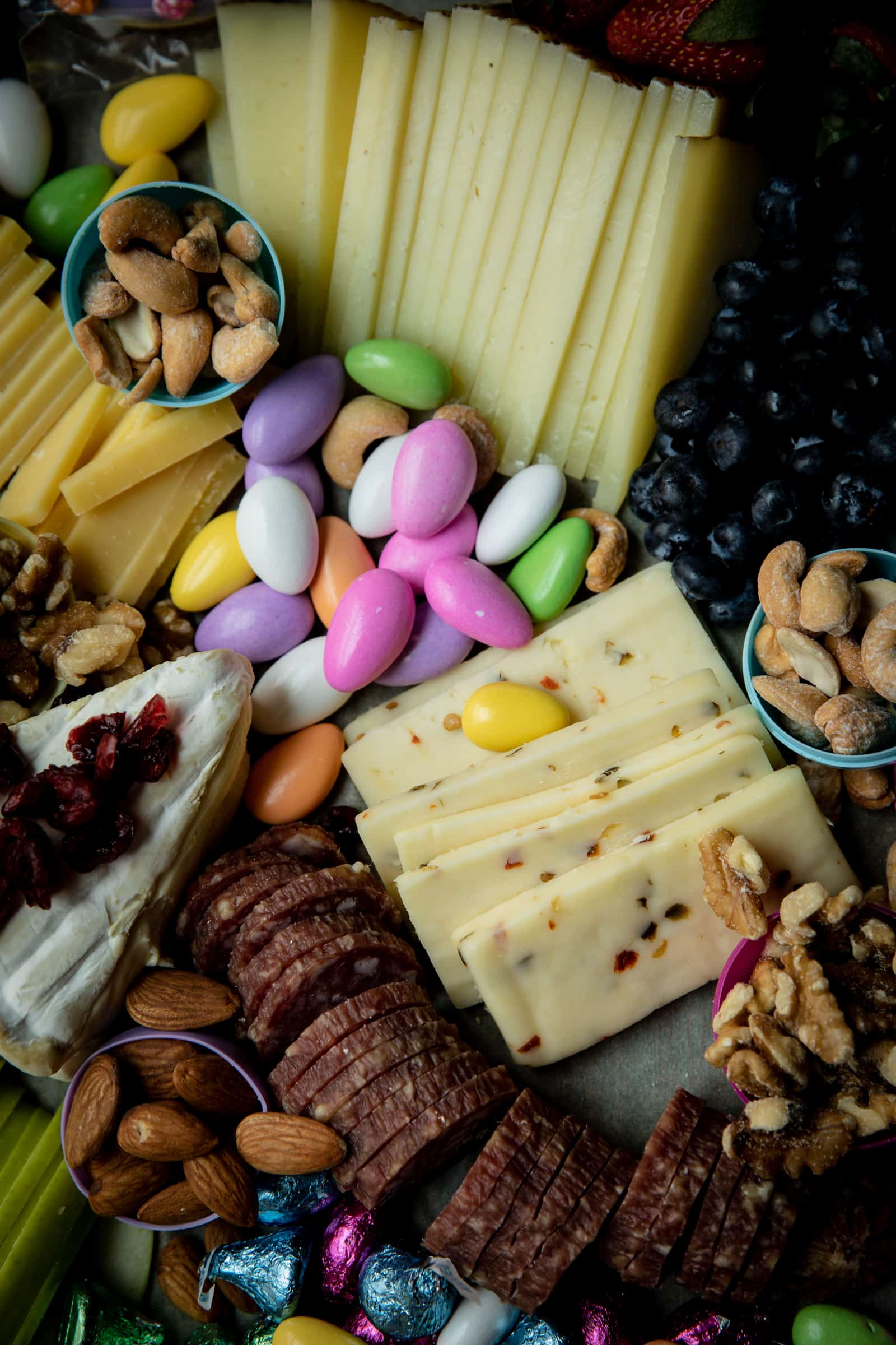 Middle of cheese board with chocolate covered almonds and cheese.
